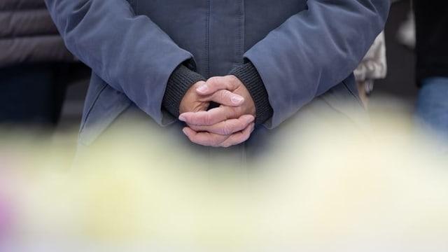 Eine Person im Krichenstreik: Zu sehen sind nur die ineinander gelegten Hände.