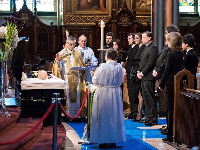 Céline Dion steht mit anderen Trauergästen an einem geöffneten Sarg.
