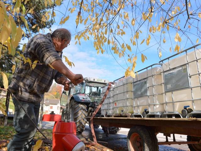 Ein Bauer füllt Wasser in Tanks, welche auf einem Anhänger stehen.