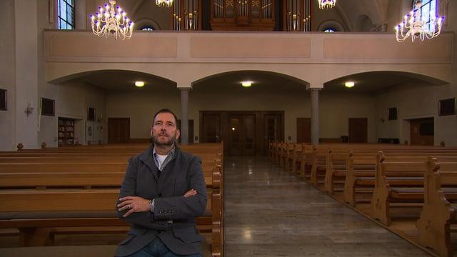 Hans-Peter Portmann, Nationalrat FDP/ZH in einer Kirche auf einer Bank sitzend.
