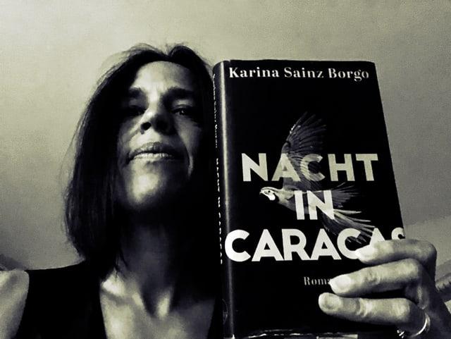 Annette König steht in einem dunklen Raum und hält Karina Sainz Borgos Roman «Nacht in Caracas» in die Kamera