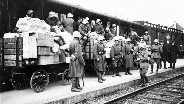 Mehrere Soldaten vor einem Zug auf einer historischen Aufnahme