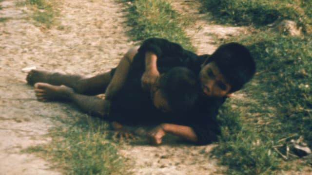 Duc Tran Van und seine Schwester liegen geduckt auf einem Feldweg.