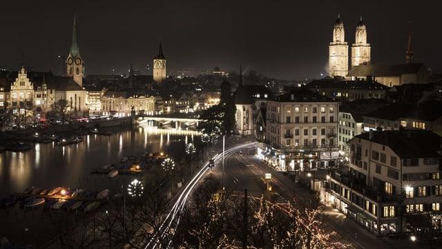 Blick auf die Zürcher Altstadt bei Nacht mit zahlreichen hell erleuchteten Kirchtürmen.