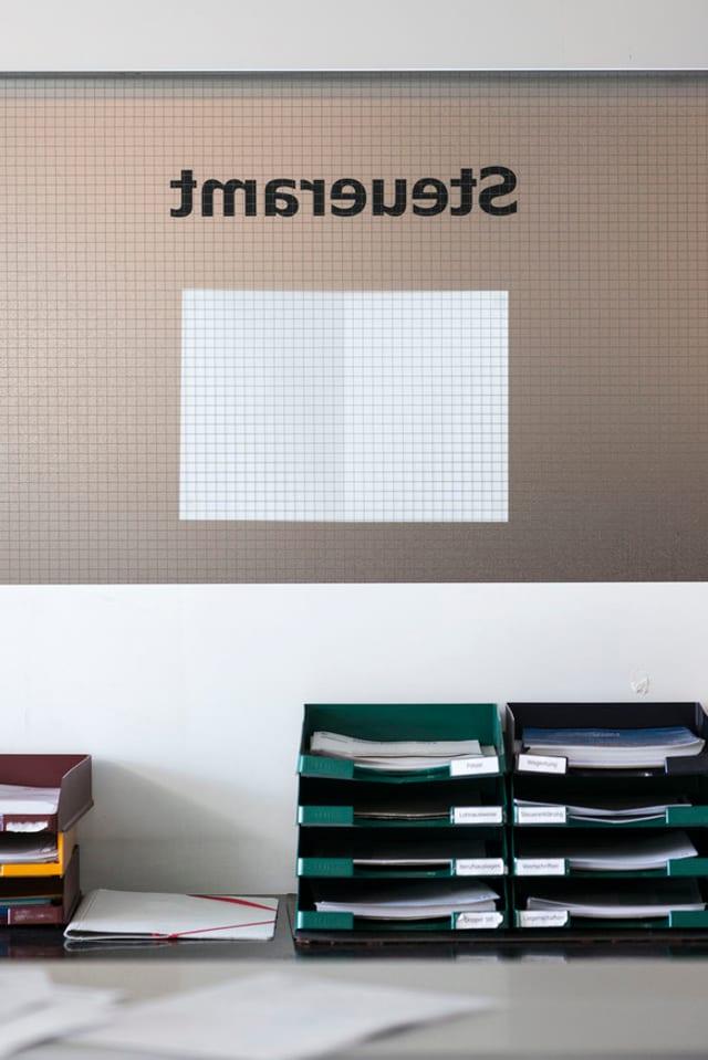 Blick in ein Büro des Steueramts mit Ablagefächern und dem Schriftzum «Steueramt»