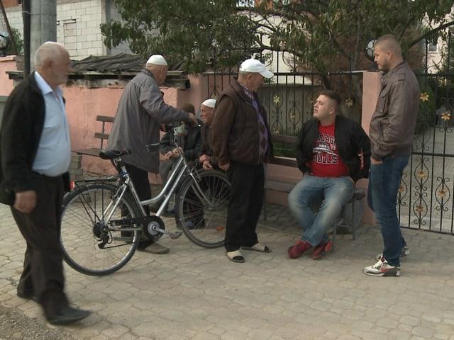 Ein paar Menschen stehen vor einer Moschee in Gjilane.