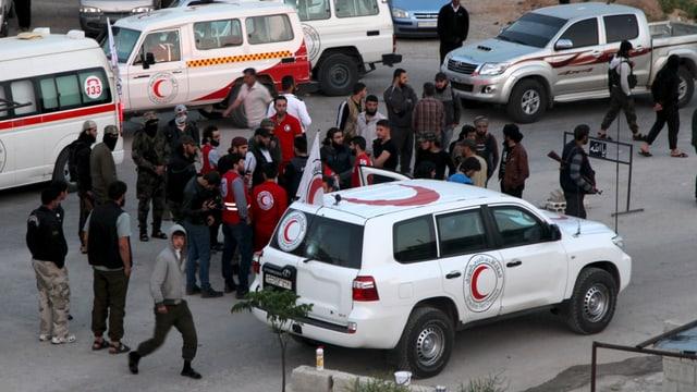 Fahrzeuge des Roten Halbmondes stehen für die Evakuation bereit, darum herumb haben sich Leute versammelt