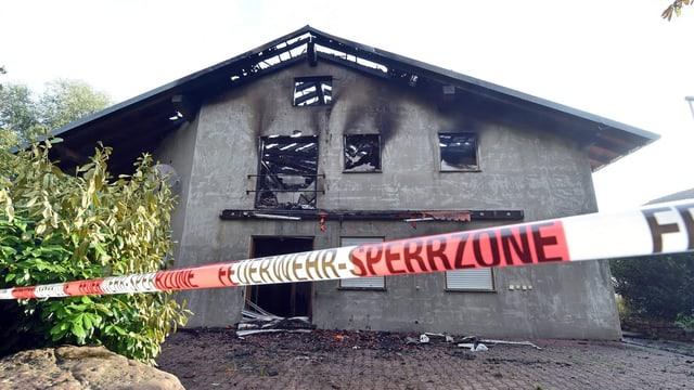 Ein ausgebranntes Haus, das mit einem Polizeiband abgesperrt ist
