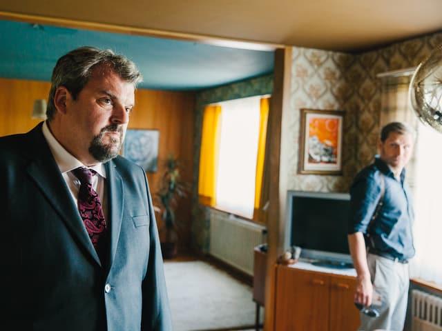Luc und Doerig stehen mit ernsten Gesichter in einem altmodisch eingerichteten Wohnzimmer.