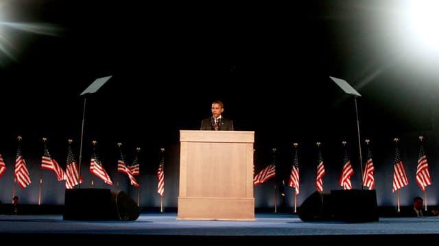 Barack Obama steht an einem Rednerpult, dahinter Amerika-Flaggen.