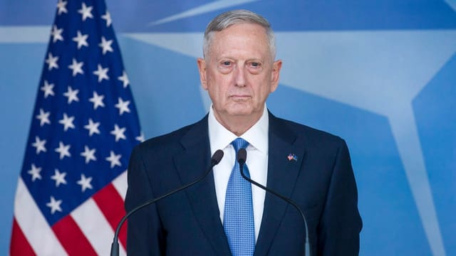 Mit geschlossenem Mund ernstem Gesicht vor einer US-Flagge am Rednerpult des Nato-Sitzes.