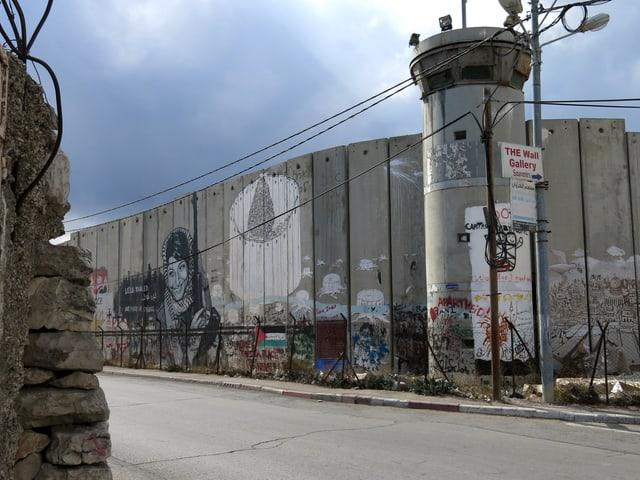 """Auf der Mauer prangt diverse Street-Art und ein Schild mit der Aufschrift """"The Wall Gallery""""."""