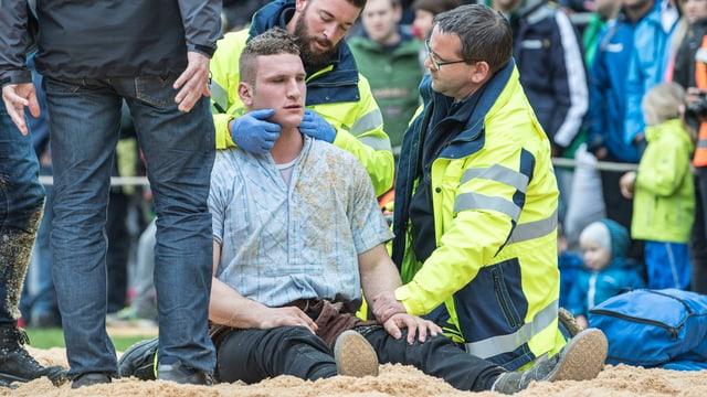 Armon Orlik sitzt im Sägemehl und wird von Sanitätern betreut