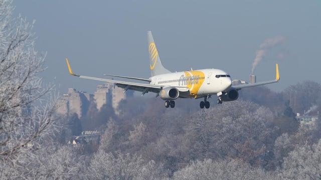Flugzeug im Landeanflug, im Hintergrund Wohnblöcke