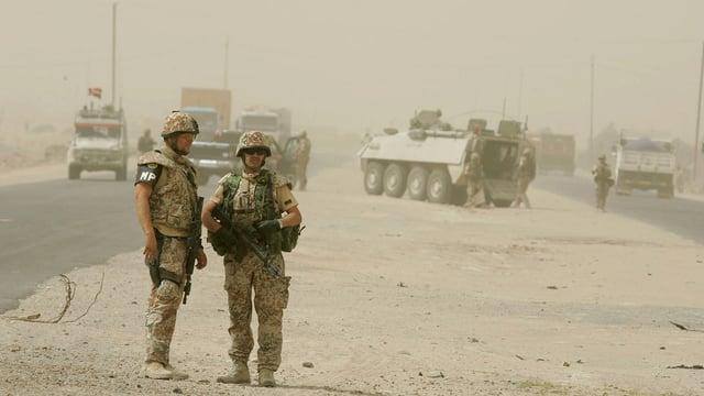 Symbolbild: Soldaten stehen in Wüstenumgebung herum, im Hintergrund gepanzerte Fahrzeuge, eines mit einer dänischen Flagge.