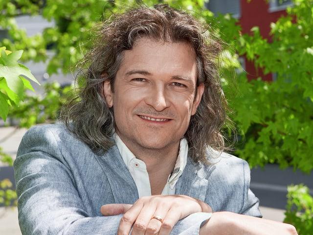Dani Häusler trägt eine weisses Hemd und eine graue Weste und posiert vor einem sanftgrünen Busch fürs Porträtbild.