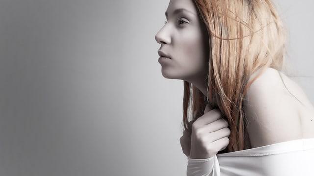 Frierende, sehr bleiche Frau zieht die Schultern hoch.