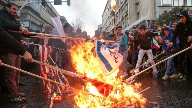 Menschen verbrennen Flaggen der USA und Israel.