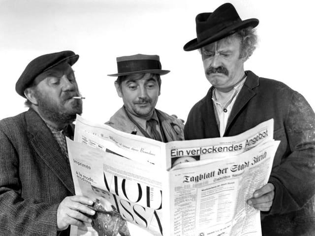 Drei Männer lesen zusammen in einer Zeitung.