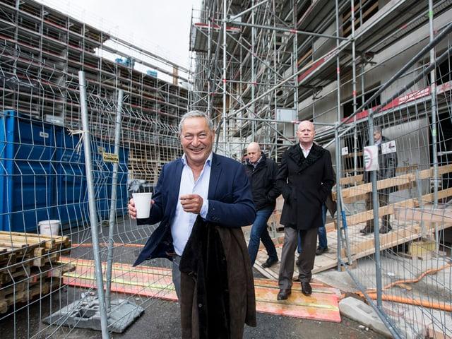Ein Mann in Anzug läuft über eine Baustelle.