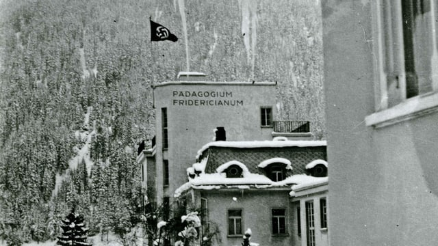 Auf einem Dach weht eine Hakenkreuz-Flagge, im Hintergrund verschneite Berge.