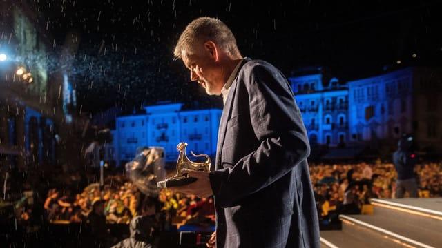Mann mit kleiner goldener Leopardenstatuette vor Publikum. Im Scheinwerferlicht ist Regen zu erkennen.