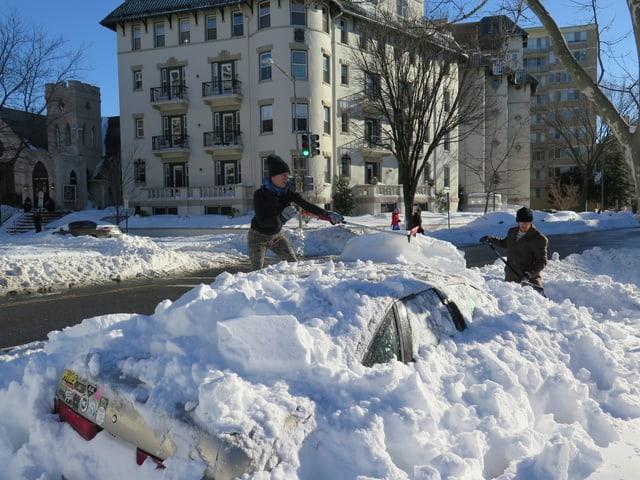 Zwei Menschen schaufeln ein mit Schnee beladenes Auto frei