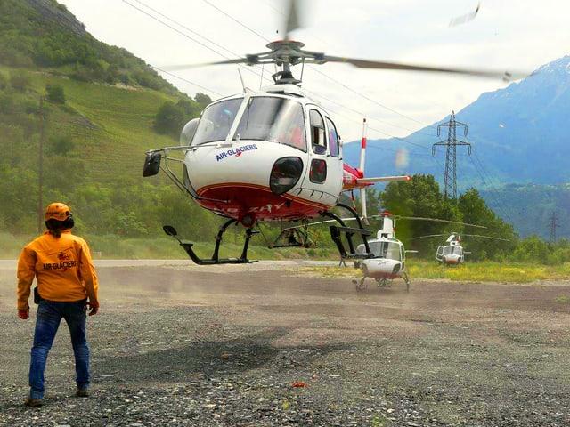 Ein Helikopter kurz vor dem Start auf einem Kiesfeld, daneben steht ein Mann.