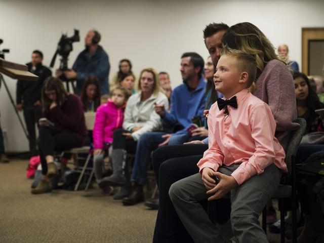 Junge sitzt bei seinen Eltern in vollem Gemeindesaal.