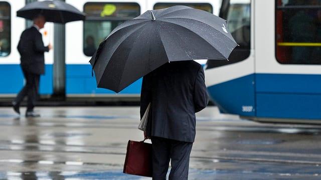 Bankmitarbeiter unter Regenschirm stehend mit einer Aktentasche in der Hand. Tram im Vordergrund