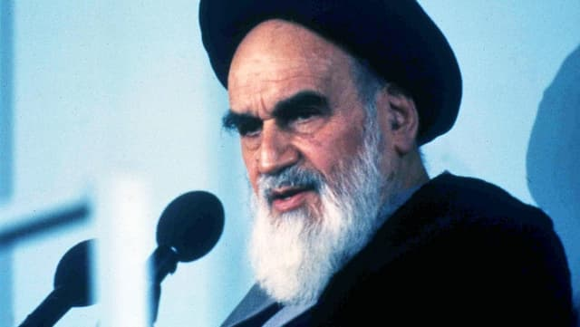 Ayatollah Chomeini mit Turban und Bart vor einem Mikrofon.
