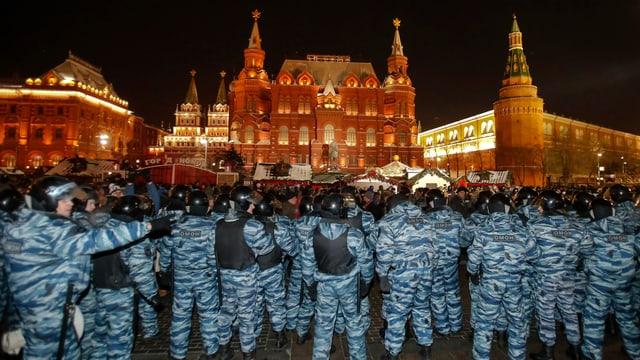 Sicherheitskräfte in Tarnanzügen mit dem Rücken zur Kamera, dahinter in der Ferne ein beleuchtetes Gebäude.