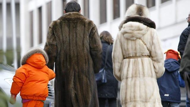 Ein Ehepaar in Pelzmantel mit Kindern