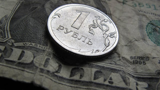 Eine Rubel-Münze liegt auf einem Dollar-Schein.