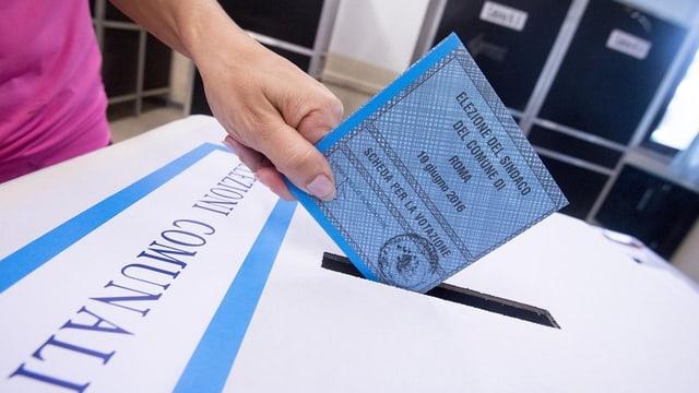 Segund scrutini da las elecziuns communalas en l'Italia - in maun metta in scrit da votar en l'urna