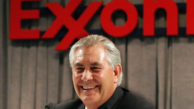 Rex Tillerson lacht in die Kamera vor dem roten Logo von ExxonMobil