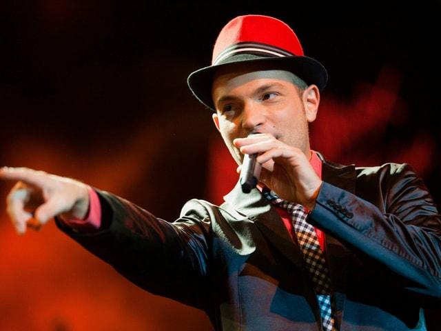 Sänger während Auftritt mit rotem Hut.