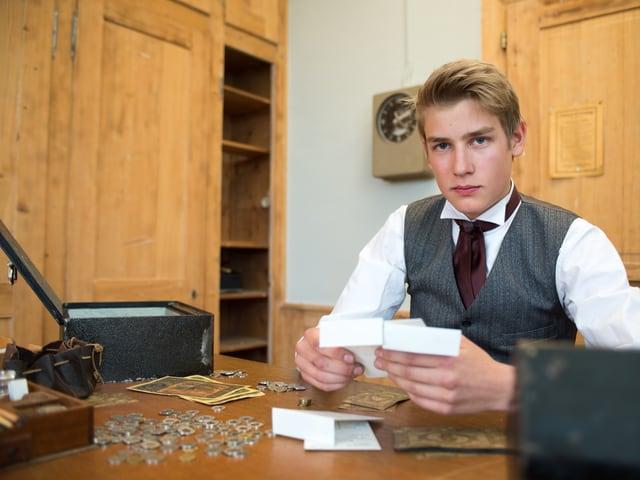 Elias im Fabrikbüro, zählt Geld und füllt es in Lohnsäckli