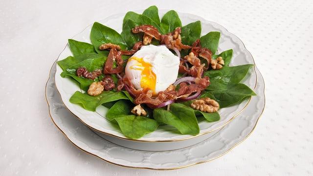 Pochiertes Ei auf Spinatsalat an Rohschinkendressing in einem weissen Suppenteller mit goldigem Rand.