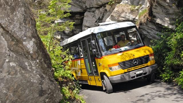 Ein Postauto fährt die Strasse zwischen zwei Felsen rauf.