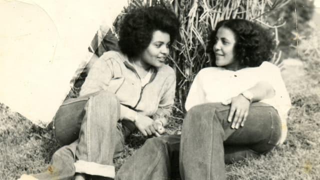 Zwei Frauen mit Jeans und weissem Pulli liegen in einer Wiese.