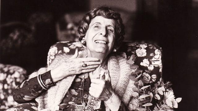 Ein Bewohnerin eines Altersheimes lachend auf einem Schwarz-weiss-Photo.