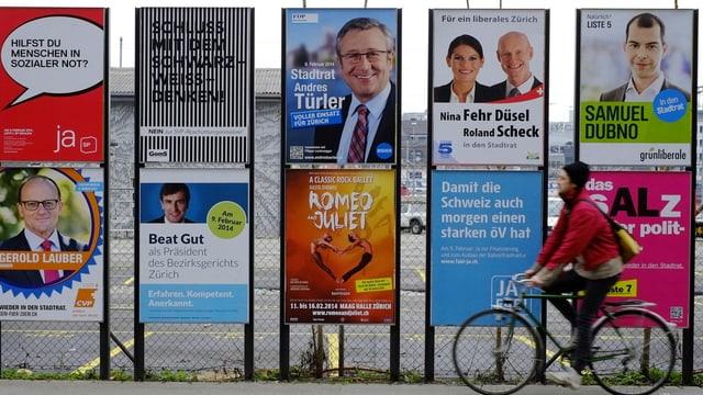 10 Wahlplakate an Plakatwänden entlang einer Strasse, davor ein vorbeifahrender Velofahrer