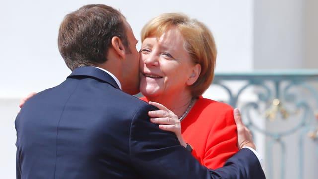 Macron begrüsst Merkel mit Wangenküsschen, Merkel lächelt.