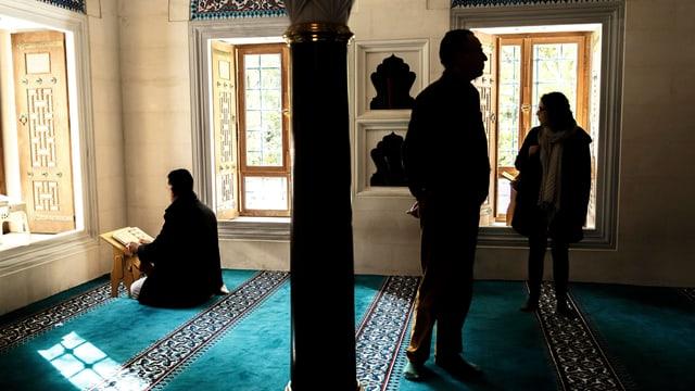 In einem kleinen Gebetsraum: Zwei Besucher sehen sich am Tag der offenen Türe die Berliner Sehitlik Moschee an, während ein Muslime darin betet.