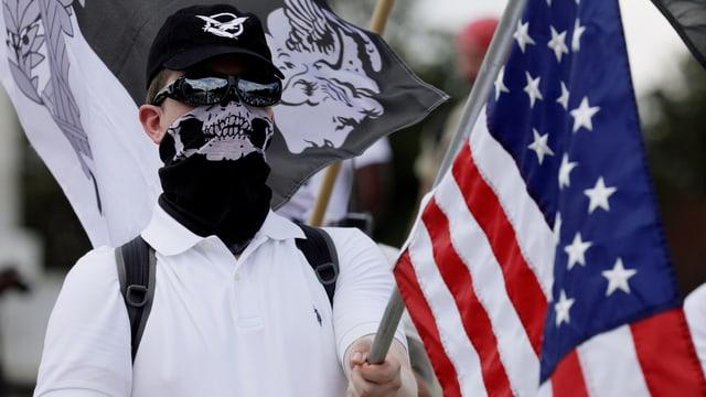 Vermummter Rechtsextremer mit US-Flagge