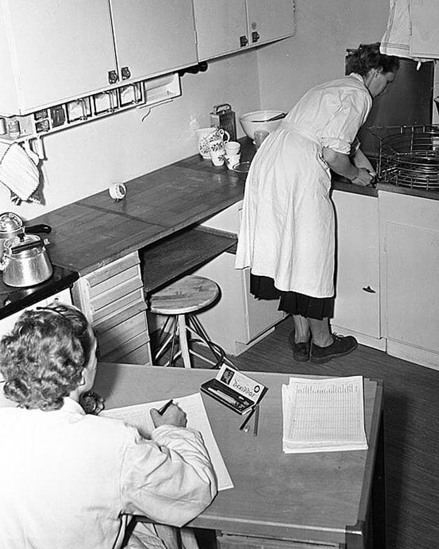 Eine Frau in der Küche, jemand sitzt daneben am Tisch und schreibt auf ein Papier.