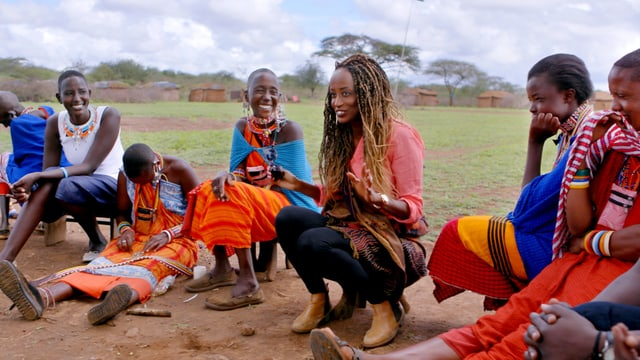 Eine dunkelhäutige Frau spricht zu einer Gruppe lachender Frauen.