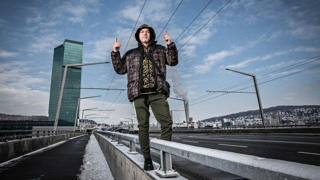 Mann steht am Rand einer Strasse vor einem Hochhaus und zeigt mit beiden Zeigefingern nach oben
