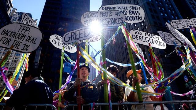 Demonstranten vor Hochhäusern halten Schilder in die Höhe.